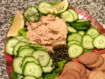 Photo of Salmon Dip on a bed of lettuce with cucumbers, crackers, capers, and lemons / www.super-seafood-recipes.com