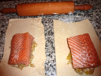 Photo of Salmon filets placed on top of leek mixture on puff pastry rectangles/ www.super-seafood-recipes.com
