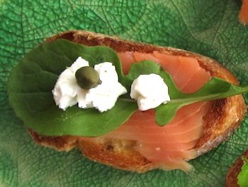 Photo of Bruchetta with smoked salmon, arugula, dabs of goat cheese, and capers / www.super-seafood-recipes.com