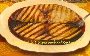 Photo of grilled swordfish steaks on a platter ready to serve with the Sicilian sauce